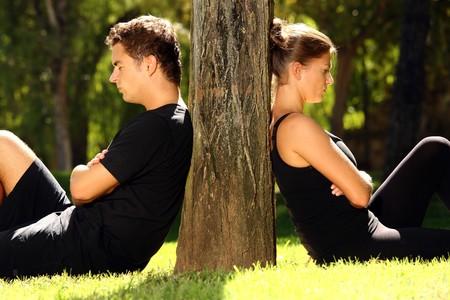 persona triste: Una imagen de una joven pareja sentada en el parque y est�n en un conflicto