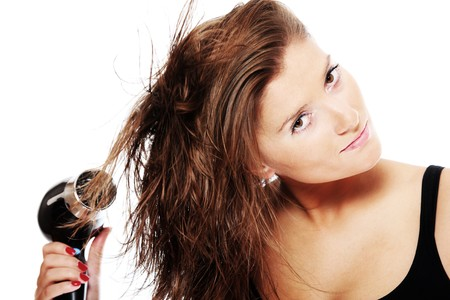 A portrait of a young pretty woman drying her hair over white background photo