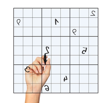 A close up of a female hand solving sudoku over white background photo