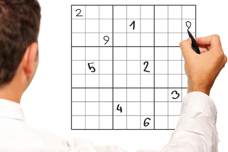 A close up of a male hand solving sudoku over white background photo