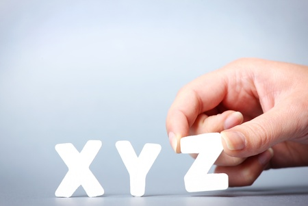 A picture of female hand putting letters xyz in a row