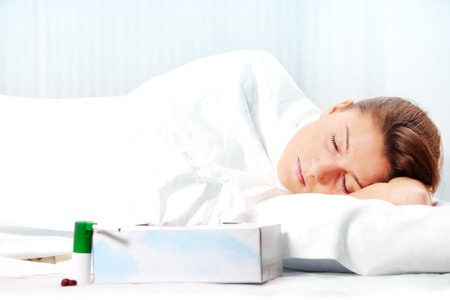 A portrait of a young woman sleeping in bed having flu over white background photo