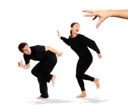 gevangen: Een afbeelding van jonge paar weglopen van grote hand, een heleboel conceptuele betekenissen