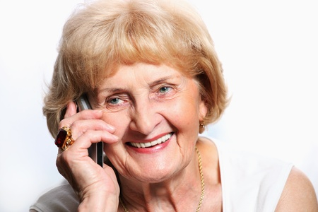 A portrait of a pretty senior lady talking on the phone over white background photo