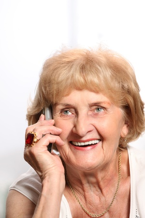 A portrait of a smiling senior lady talking on the phone over white background photo