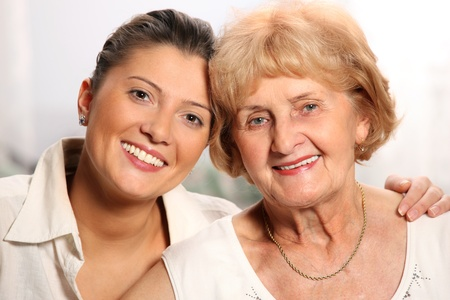 grandaughter: A beautiful portrait of grandma and grandaughter smiling over white background
