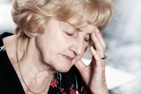 A portrait of a senior lady having headache over dark background Stock Photo - 8653592