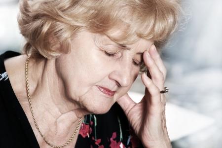 hoofdpijn: Een portret van een senior dame die hoofd pijn over donkere achtergrond Stockfoto