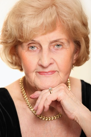 A nice portrait of a senior lady sitting against white background photo