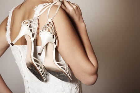 wornout: A portrait of the back of the bride carrying worn-out shoes Stock Photo