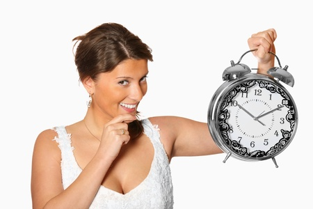 A portrait of a pretty young bride with an alarm clock against white background photo