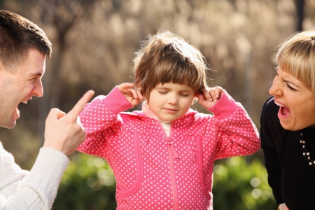 girl fighting: A picture of parents shouting at a little girl in the park Stock Photo