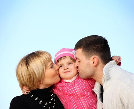 A picture of parents kissing their little girl over blue sky, a lot of space for text