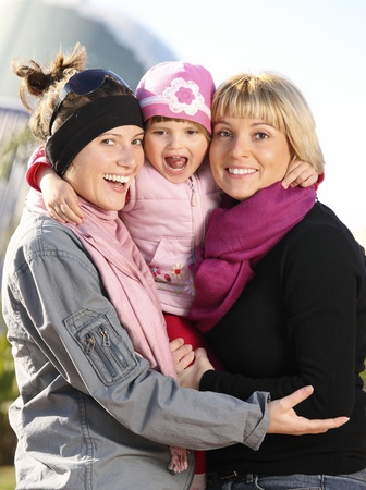 A picture of a happy baby girl spending time in the park with her mum and aunt photo