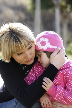 beautiful crying woman: A picture of a mum comforting and hugging her baby girl in the park