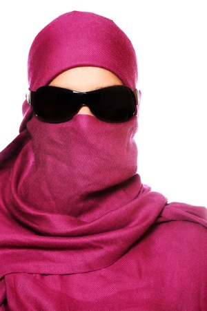 face covered: A portrait of an arabic woman face hidden behind a purple scarf