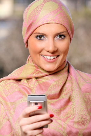 face covered: A portrait of a successful arabic woman using the cell phone