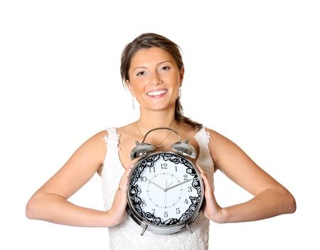 A picture of a pretty bride holding a clock over white background photo