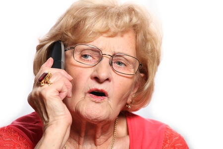 A portrait of an elderly lady talking on the phone against white background photo