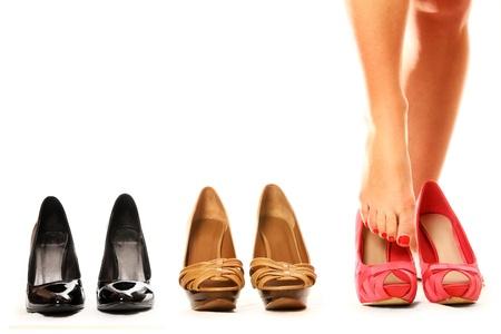 Una foto de una mujer poniendo en zapatos nuevos sobre fondo blanco Foto de archivo