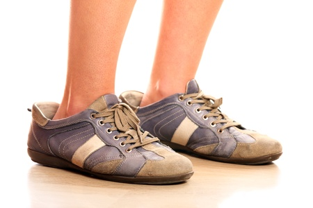 A closeup of female legs trying on too big male shoes over white background photo