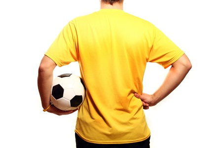 A picture of a young footballer in a yellow t-shirt with a football over white background photo