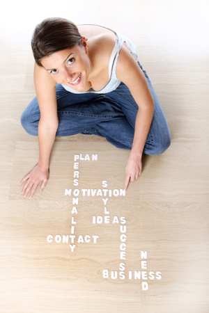 A picture of a young woman sitting on the floor and creating a business crossword Stock Photo - 9046570