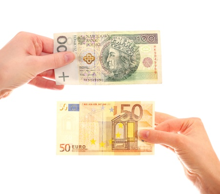 A picture of hands holding Polish hundred-zloty note and fifty-euro note over white background photo
