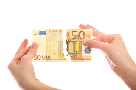 euro banknote: A picture of hands tearing fifty-euro note over white background