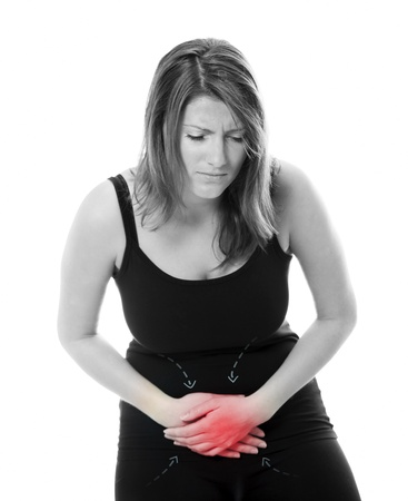upset woman: A picture of a young woman suffering from stomach ache against white background Stock Photo