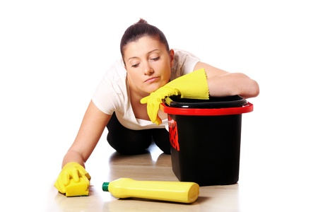 housewife gloves: A picture of a young tired housewife cleaning the floor over light background Stock Photo