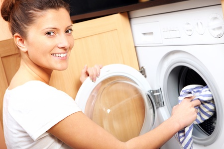 A close up of a young wife putting a cloth into washing machine Stock Photo