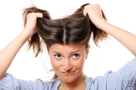 A portrait of a young frustrated woman pulling out hair over white background Stock Photo - 9112879