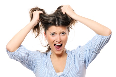 pulling hair: A portrait of a young frustrated woman pulling out hair over white background Stock Photo