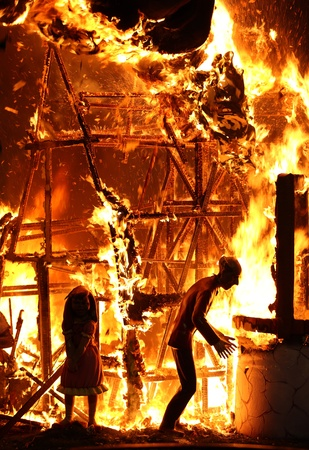 damaged house: A picture of a house on fire and two mannequins inside