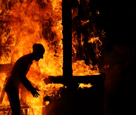 burning man: A picture of a mannequin of an old man escaping from the house on fire