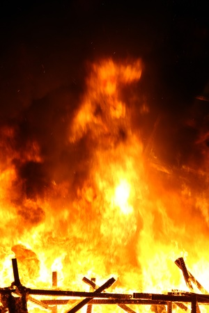 devouring: A picture of smoking ruins with big flames during the night