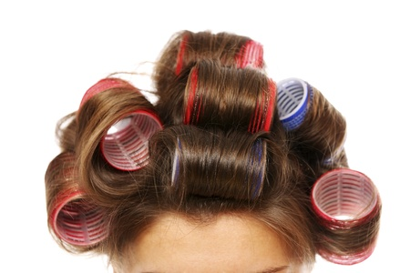 A close up of a female head with curlers on over white background