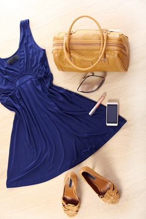 A set of female must haves including: dress, bad, heels, sunglasses, lipgloss and a cellphone photo