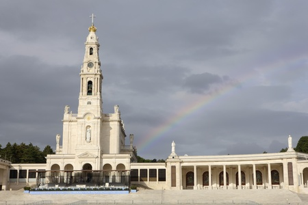 A picture of a beautiful old church in Fatima over a sky background and a rainbow on it photo
