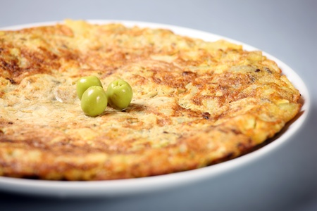 A picture of a typical Spanish tortilla decorated with olives over light background photo
