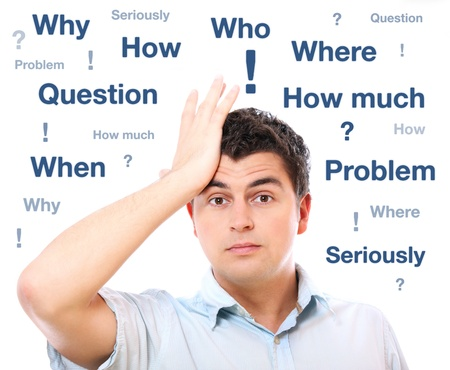 A portrait of a young handsome man with questions holding his head over light background Stock Photo - 9264129