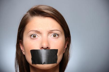 kokhalzen: Een foto van een jong meisje met haar lippen bedekt door een tape grijze achtergrond Stockfoto
