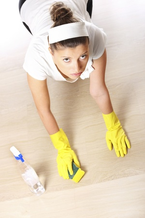 A picture of a young woman cleaning the floor over light background photo