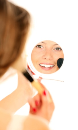 A picture of a mirror reflection of a beautiful girl putting on make-up photo