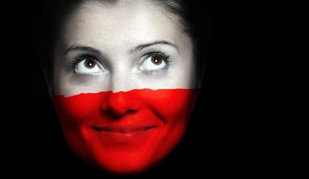bandera de polonia: A cerca de una bandera polaca en un rostro femenino sobre fondo negro