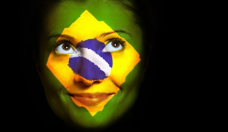 femal: A close up of a Brazilian flag on a femal face over black background