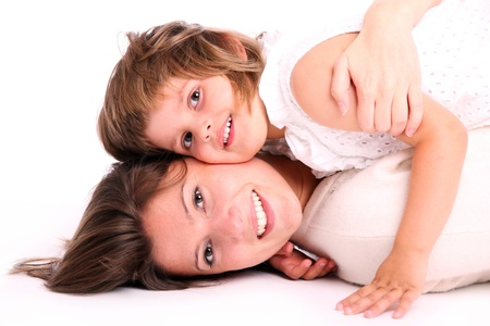 A portrait of a mother and her baby girl lying on the floor and hugging over white background photo