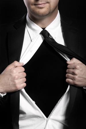 shirt unbuttoned: Una foto di un bel giovane strappo fuori la sua camicia su sfondo nero