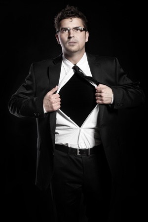 A picture of a young handsome man tearing off his shirt over black background Stock Photo - 9780848